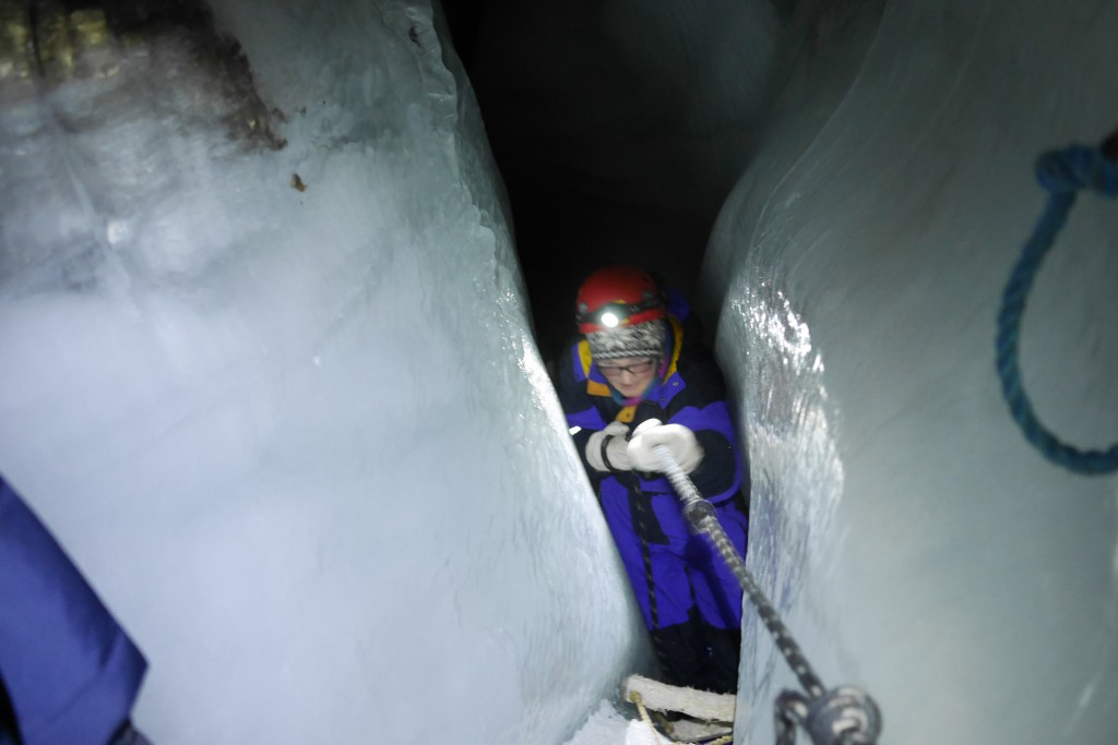 Mette klatrer opp en av de åletrange trappene ned i isgrotta. Foto: Carina Alice Bredesen